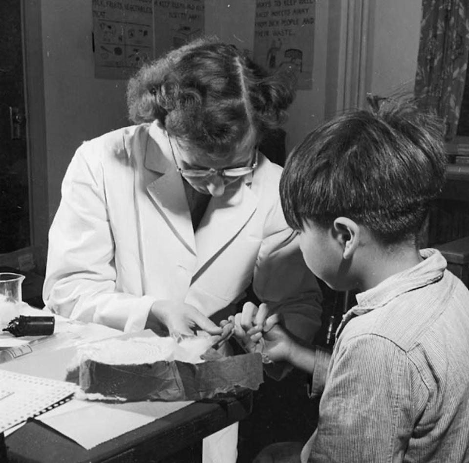 Black and white photo: a nurse takes a blood sample from a little boy