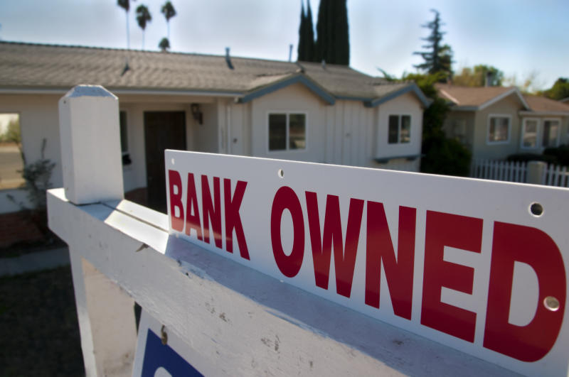 A foreclosed home shows a bank owned for sale sign.