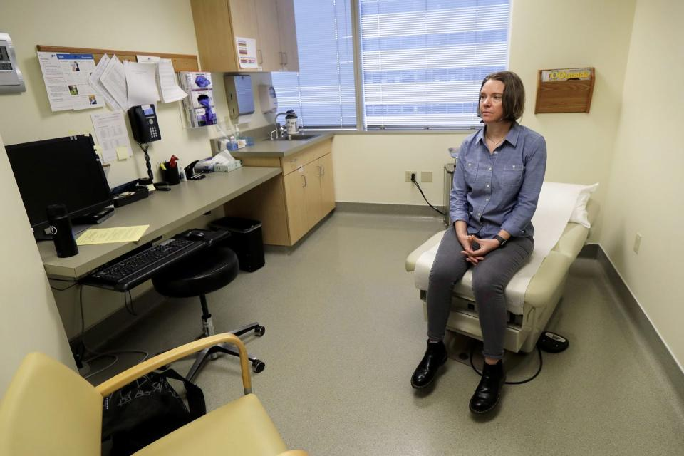 A woman in jeans and a denim shirt sits on the end of an exam table in a medical exam room.