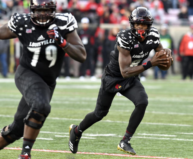 Louisville quarterback Lamar Jackson (8) runs the ball behind the blocking of Louisville offensive lineman Kenny Thomas (79) during the first half of an NCAA college football game, Saturday, Nov. 11, 2017, in Louisville, Ky. (AP Photo/Timothy D. Easley)