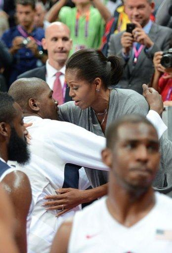 US First Lady Michelle Obama congratulates the US basketball players after they won 98-71 the Men's Preliminary Round Group A match United States vs France at the London 2012 Olympic Games in London