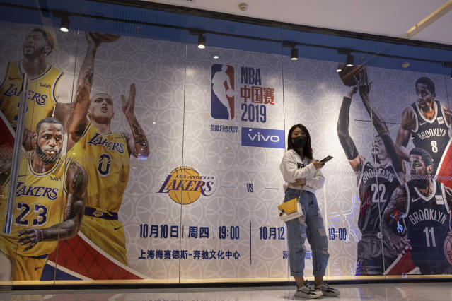 "In this Friday, Oct. 11, 2019, photo, a woman wearing a mask stands near promotion boards for a NBA preseason game between Brooklyn Nets and Los Angeles Lakers in Beijing. When Houston Rocket's general manager Daryl Morey tweeted last week in support of anti-government protests in Hong Kong, everything changed for NBA fans in China. A new chant flooded Chinese sports forums: ""I can live without basketball, but I can't live without my motherland.""(AP Photo/Ng Han Guan)"
