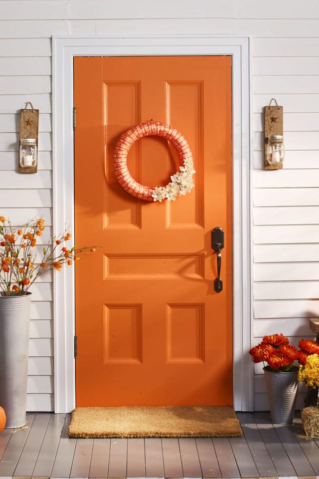 """<p>Embellish the bottom of this festive fall wreath with flowers fashioned from dried corn husks.</p><p><strong>1. </strong>Wrap plaid ribbon around <span>18</span>"""" wreath form; secure with hot glue.</p><p><strong>2. </strong>For flowers, soak corn husks in room-temperature water for two minutes; remove and blot excess water. To make a few petals at once, accordion-fold corn husk into <span>1</span>""""-wide sections, then cut out <span>1</span>"""" teardrop-shaped petal. Repeat as needed and to make <span>1</span>½"""" and <span>2</span>½"""" petals.</p><p><strong>3. </strong>Cut a <span>1</span>""""-wide corn husk strip, fold in half lengthwise, roll into tight swirl, and hot-glue onto a small cardboard circle. Hot-glue on petals, working big to small, back to front.</p><p><strong>4. </strong>Hot-glue flowers to wreath.</p><p><strong>What you'll need: </strong><span><em>Orange plaid ribbon ($12; <a rel=""""nofollow"""" href=""""https://www.amazon.com/Homeford-FHV000033544-Checkered-Christmas-Ribbon/dp/B013PWLU2Q?tag=syndication-20"""">amazon.com</a>)</em></span></p>"""