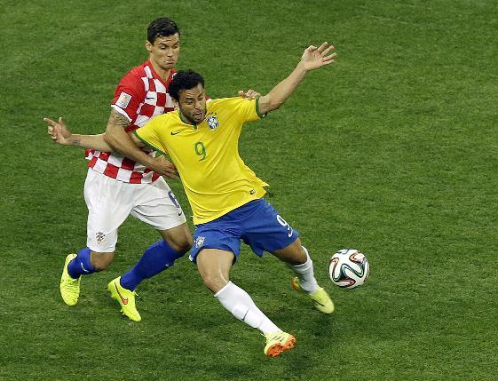 Brazil's Fred, right, falls after making contact with Croatia's Dejan Lovren during the group A World Cup soccer match between Brazil and Croatia, the opening game of the tournament, in the Itaquerao Stadium in Sao Paulo, Brazil, Thursday, June 12, 2014. (AP Photo/Thanassis Stavrakis)