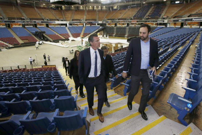 FILE — In this April 6, 2020, file photo, California Gov. Gavin Newsom, left, accompanied by Jason Kenney, deputy director of the Real Estate Services Division of the Department of General Services, tours Sleep Train Arena while it was being transformed into a 400-bed emergency field hospital in Sacramento, Calif. California spent nearly $200 million to set up, operate and staff alternate care sites that ultimately provided little help when the state's worst coronavirus surge spiraled out of control last winter, forcing exhausted hospital workers to treat patients in tents and cafeterias. (AP Photo/Rich Pedroncelli, Pool, File)
