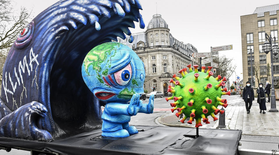 A political carnival float depicting climate and coronavirus crisis is driving in the streets of Duesseldorf Duesseldorf, Germany, Monday, Feb. 15, 2021. Because of the coronavirus pandemic the traditional 'Rosenmontag' carnival parade are canceled but eight floats are pulled through the empty streets in Duesseldorf, where normally hundreds of thousands of people would celebrate the street carnival. (AP Photo/Martin Meissner)