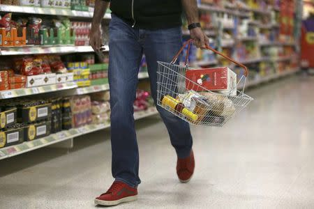 A shopper carries a basket in a supermarket in London