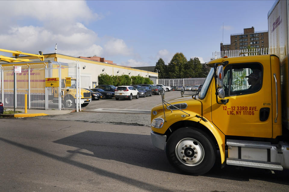 A DHL delivery truck passes a DHL location Tuesday, Oct. 20, 2020, in New York. Retailers and carriers are preparing for a holiday shipping surge that could mean delays in holiday gifts. Carriers are ramping up their holiday hiring while asking store clients to move their shipping volume on lighter days in their network. (AP Photo/Frank Franklin II)