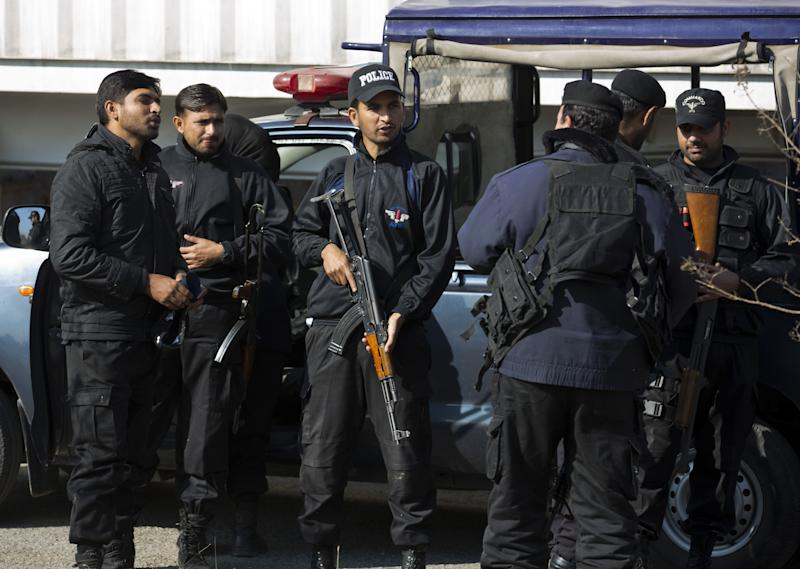 """Pakistani police commandos stand alert outside a court in Islamabad, Pakistan, Thursday, Jan. 2, 2014. Former President Pervez Musharraf was rushed to the hospital Thursday with a """"heart problem"""" while he was on his way to court for a hearing in his high treason case, said police and his lawyers. (AP Photo/B.K. Bangash)"""