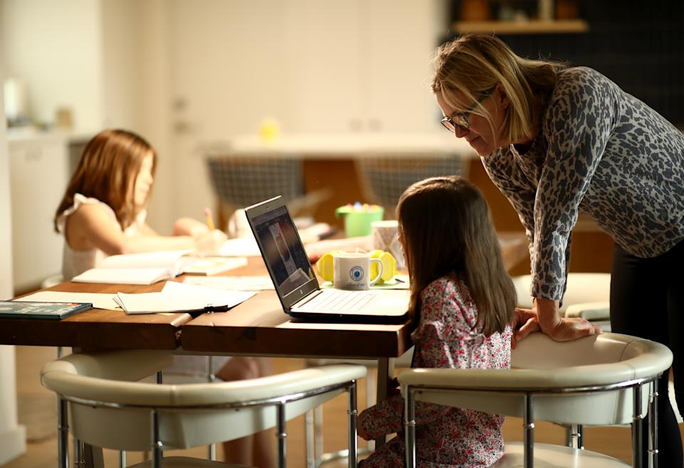 SAN ANSELMO, CALIFORNIA - MARCH 18:  Daisley Kramer helps her kindergarten daughter, Meg, with schoolwork at home on March 18, 2020 in San Anselmo, California. Fourth grader Lucy Kramer is also sitting at the table doing schoolwork. California Governor Gavin Newsom warned yesterday that schools are unlikely to reopen in the coming weeks and will more than likely remain closed until the summer break.  (Photo by Ezra Shaw/Getty Images)