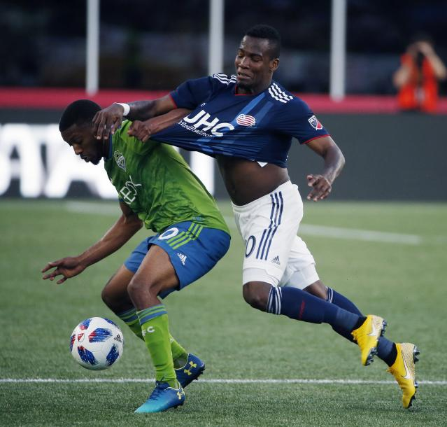 Seattle Sounders' Jordan McCrary, left, and New England Revolution's Cristian Penilla battle for the ball during the first half of an MLS soccer game in Foxborough, Mass., Saturday, July 7, 2018. (AP Photo/Michael Dwyer)