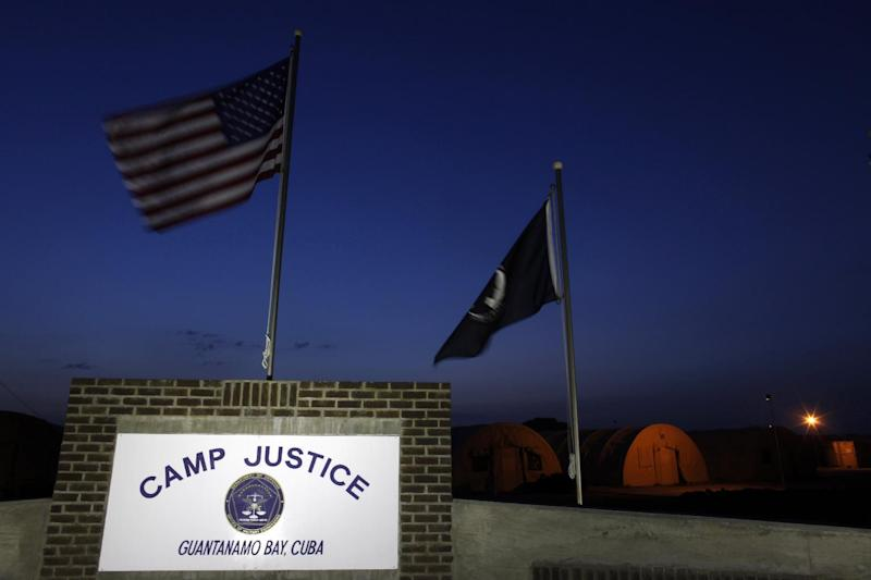 """FILE - In this July 15, 2009 file photo, reviewed by the U.S. military, flags wave above the sign for Camp Justice, the site of the U.S. war crimes tribunal compound, at Guantanamo Bay U.S. Naval Base, Cuba. Rebuffing President Barack Obama's latest plea, House Republicans would keep open the military-run prison at Guantanamo Bay, Cuba, by barring the administration from spending money to transfer terror suspects to the United States or a foreign country such as Yemen. The provisions dealing with the fate of the 166 prisoners are part of a defense policy bill drafted by Armed Services Committee Chairman Rep. Howard P. """"Buck"""" McKeon, R-Calif. The chairman released the bill Monday, two days before Republicans and Democrats on the committee will vote on the measure. (AP Photo/Brennan Linsley, Pool)"""