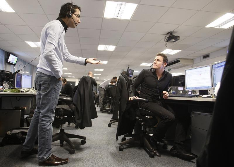 Traders work on a trading floor in London