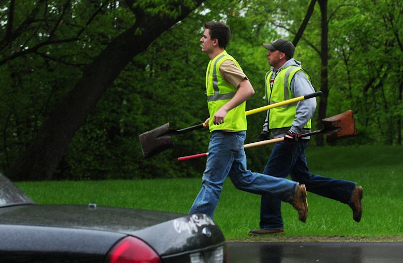 Workers with shovels run to the staging area for a rescue operation underway on the West Side of St. Paul, Minn.,  Wednesday, May 22, 2013. One child on a school field trip was killed and another remained unaccounted after a gravel slide Wednesday in a St. Paul park that's popular with children looking for fossils, authorities said.   (AP Photo/The St. Paul Pioneer Press, Scott Takushi)  MINNEAPOLIS STAR TRIBUNE OUT