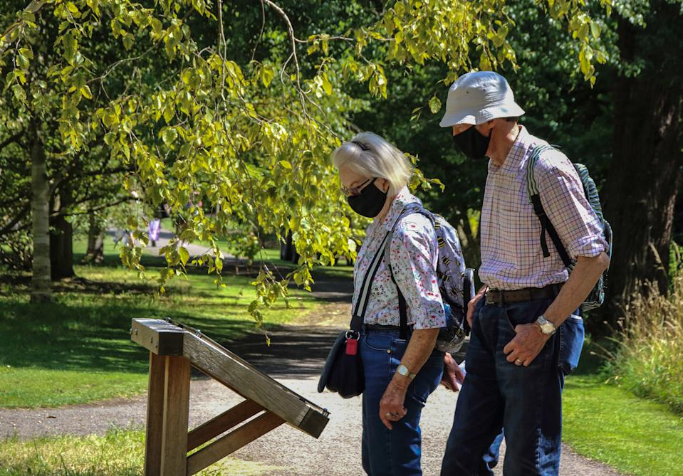 An elderly couple wearing face masks walk along the park. People wear a variety of facemasks outdoors in Cambridge, although they are only mandatory on public transport and inside shops and public spaces at the moment in the UK. (Photo by Keith Mayhew / SOPA Images/Sipa USA)