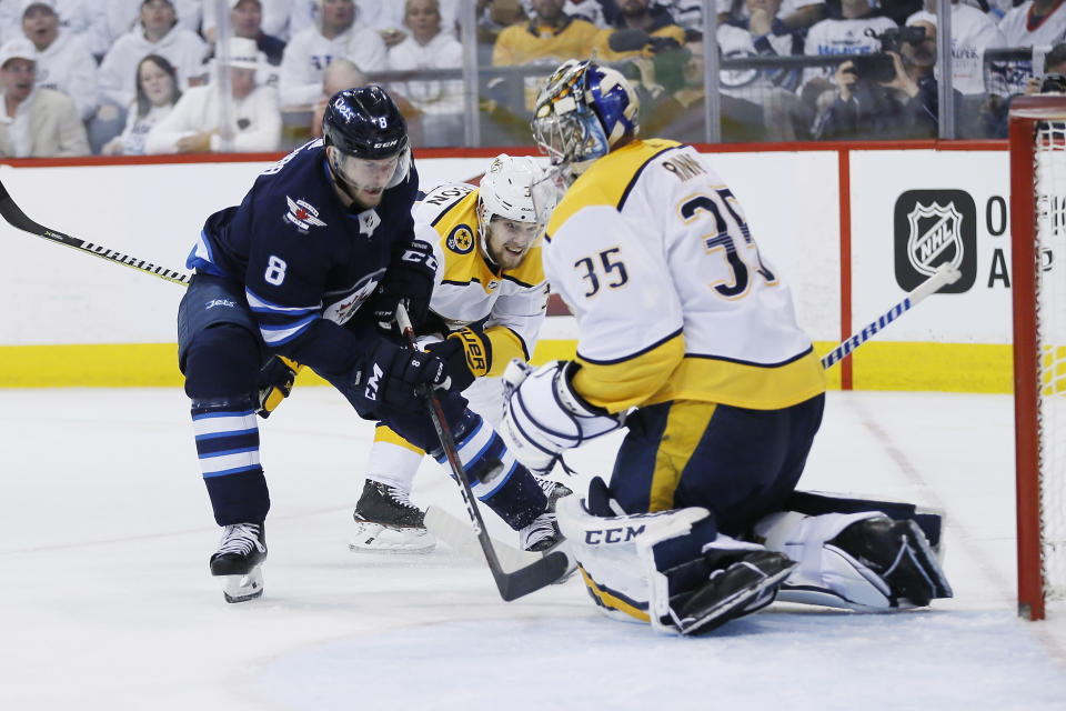 A shot by Winnipeg Jets' Jacob Trouba's (8) is stopped by Nashville Predators goaltender Pekka Rinne (35) as Viktor Arvidsson (33) defends during the second period of Game 4 of an NHL hockey second-round playoff series in Winnipeg, Manitoba, Thursday, May 3, 2018. (John Woods/The Canadian Press via AP)