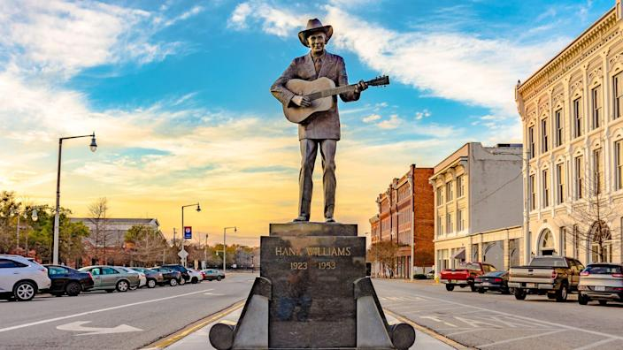 Statue of Hank Williams, the famous country singer,  on Commerce Street in Montgomery, Alabama with historic buildings on the right.