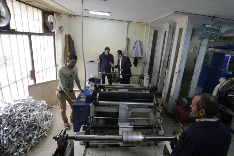 "In this Monday, March 3, 2014 photo, Adel Abd ElSadk, owner of the pharmaceutical packaging company Trustpack, second right, talks with an employee manning one of the machines at his factory which has been financed in part by loans from the Social Development Fund, located just outside Cairo, Egypt. The program, called ""The Project"" in Arabic, highlights entrepreneurship and small business acumen - something experts say is more crucial than ever as Egypt tries to claw its way out of tough economic times. (AP Photo/Amr Nabil)"