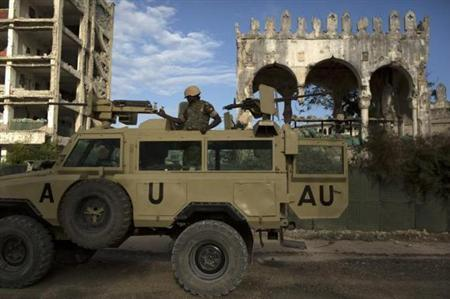 An African Mission in Somalia (AMISOM) soldier keeps guard on top of an armoured vehicle in the old part of Mogadishu
