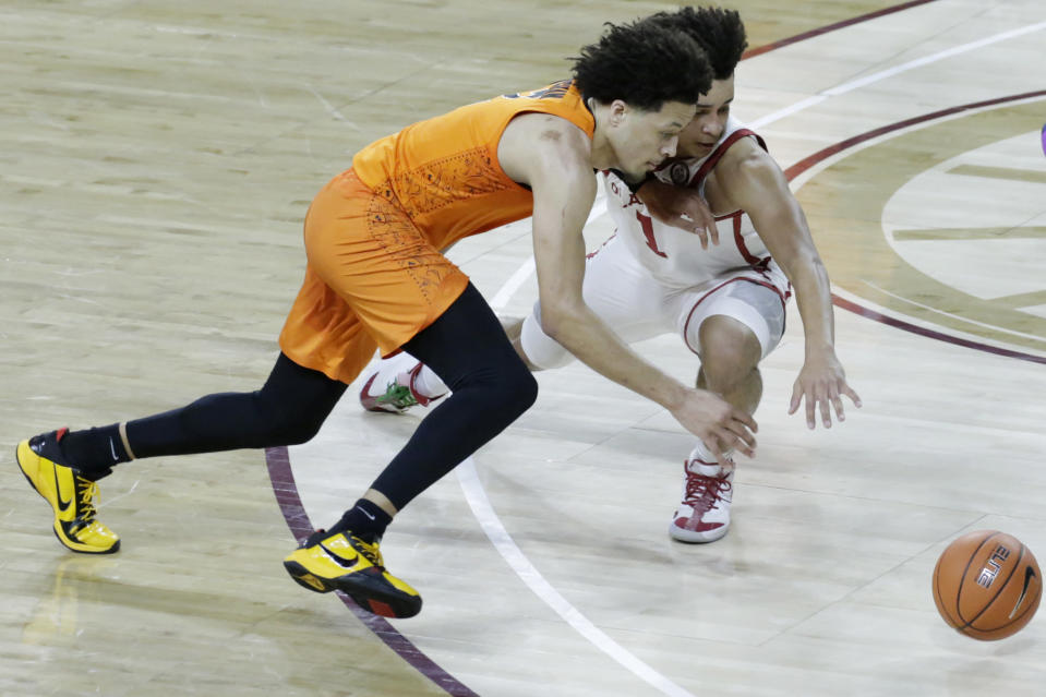 Oklahoma State guard Cade Cunningham (2) and Oklahoma forward Jalen Hill (1) fight for the ball during the first half of an NCAA college basketball game, Saturday, Feb. 27, 2021, in Norman, Okla. (AP Photo/Garett Fisbeck)