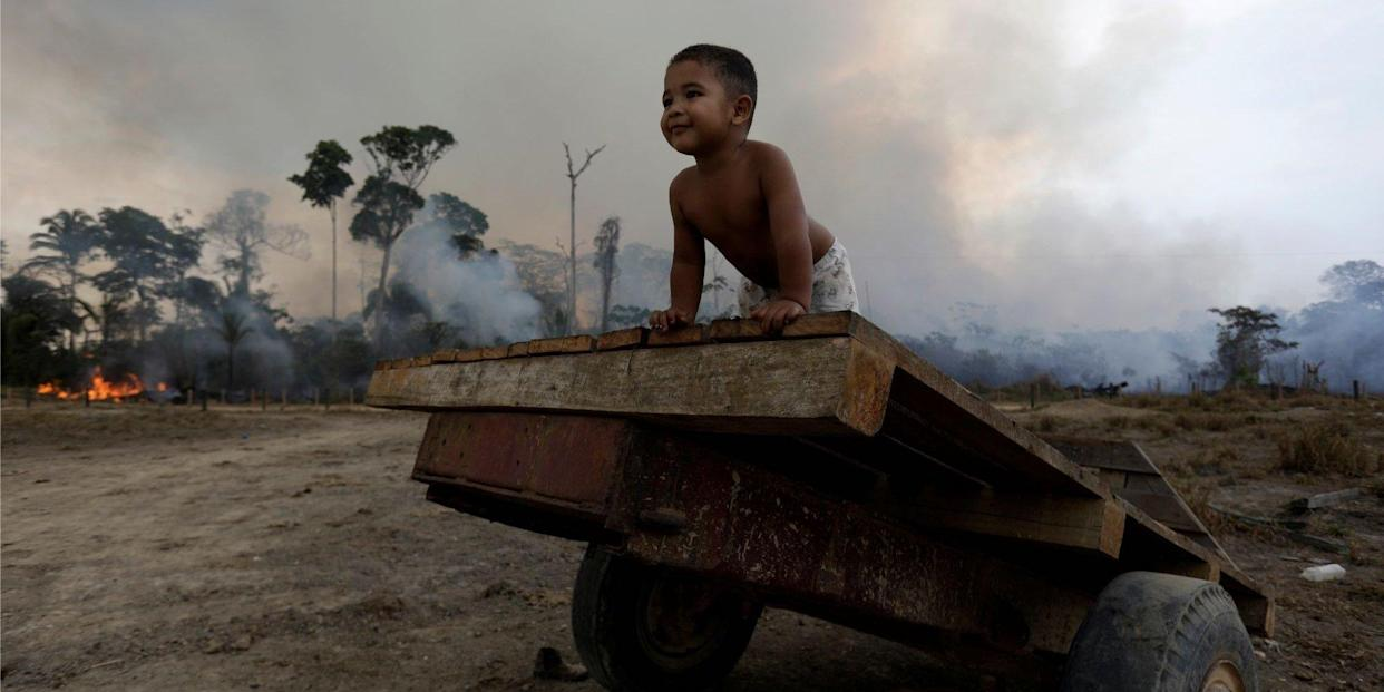Jose, 2, plays while a fire burns a tract of Amazon jungle as it is cleared by loggers and farmers near Porto Velho, Brazil August 27, 2019.