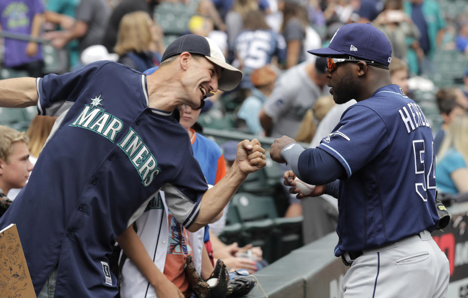 A fan, left, fist-bumps Tampa Bay Rays' Guillermo Heredia as Heredia gives autographs before a baseball game against the Seattle Mariners, Sunday, Aug. 11, 2019, in Seattle. (AP Photo/Ted S. Warren)