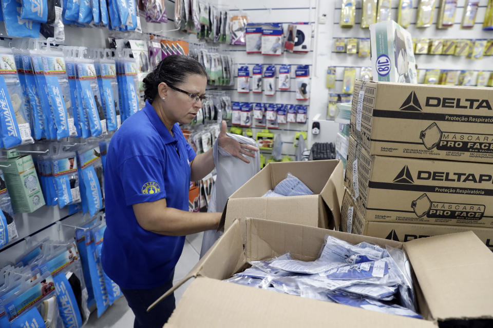 A medical supply store worker organizes masks that customers are buying as a precaution against the spread of the new coronavirus COVID-19, in Sao Paulo, Brazil, Wednesday, Feb. 26, 2020. Brazil's government confirmed on Wednesday that a Brazilian man who traveled to Italy this month has Latin America's first confirmed case of the contagious new coronavirus. (AP Photo/Andre Penner)