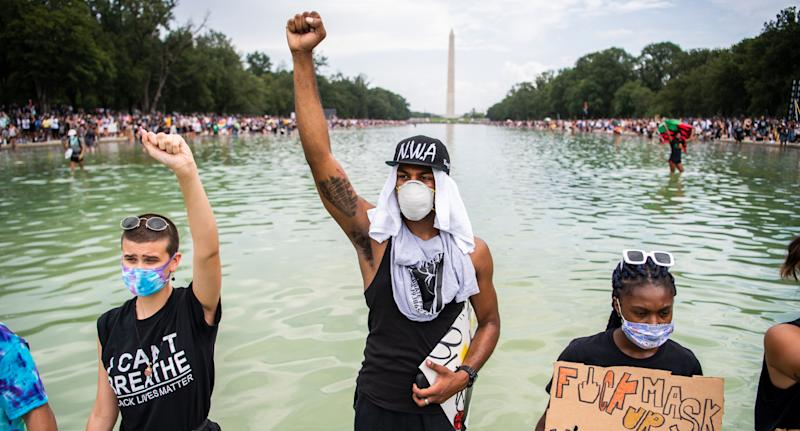 Demonstrators stand in the Lincoln Memorial Reflecting Pool as thousands rallied. Source: AAP