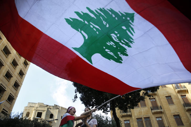 Anti-government protesters wave a large Lebanese flag during a demonstration in Beirut, Lebanon, Sunday, Oct. 20, 2019. Protests erupted in Lebanon after the government proposed new taxes criticized for hitting low income groups the hardest. (AP Photo/Hussein Malla)