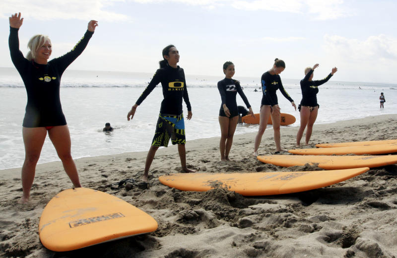 This Aug. 25, 2012 photo shows tourists taking a surfing lesson on Kuta beach, Bali, Indonesia. It can be hard to find Bali's serenity and beauty amid the villas with infinity pools and ads for Italian restaurants. But the rapidly developing island's simple pleasures still exist, in deserted beaches, simple meals of fried rice and coconut juice, and scenes of rural life. (AP Photo/Firdia Lisnawati)