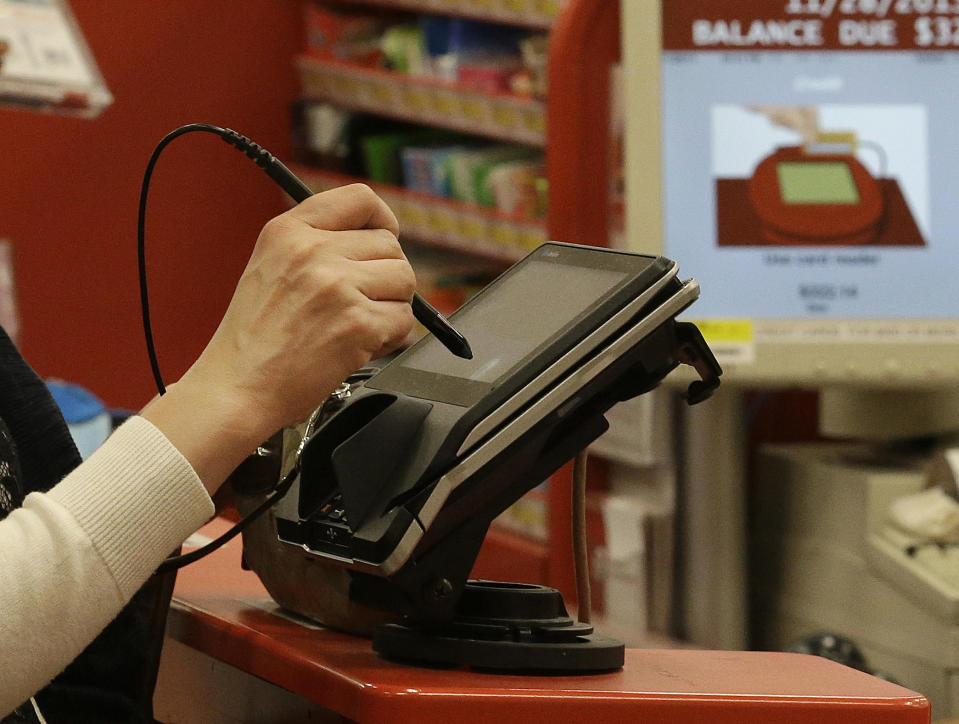 FILE - In this Thursday, Nov. 28, 2013, file photo, a woman pays by credit card while checking out at a retail store in Colma, Calif. Store credit cards may sound tempting with their discounts and loyalty incentives, but paying this way may not pay off. (AP Photo/Jeff Chiu)