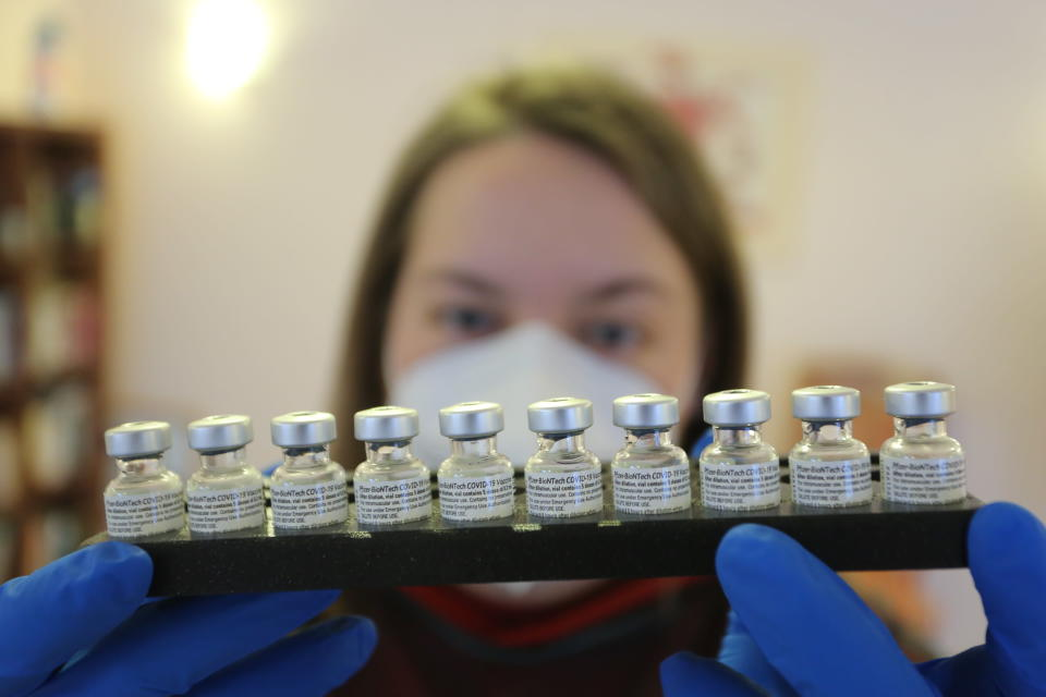An employee of a mobile vaccination team in Halberstadt holds a tray with vaccination pads from the company Biontech/Pfizer in Halberstadt, Germany, Friday, Jan.15, 2021. (Matthias Bein/dpa via AP)