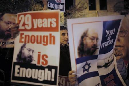 "Israelis hold placards depicting Jonathan Pollard during a protest calling for his release from a U.S. prison, outside U.S. Secretary of State John Kerry's hotel in Jerusalem January 2, 2014. The placard (R) in Hebrew reads ""To save Pollard!"". REUTERS/Ammar Awad"
