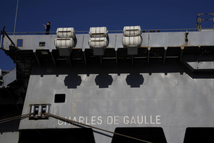 """A French crew member stands at France's nuclear-powered aircraft carrier Charles de Gaulle at Limassol port, Cyprus, Monday May 10, 2021. With the Task Force's deployment on its mission named """"Clemenceau 21,"""" France is assisting in the fight against terrorism while projecting its military power in regions where it has vital interests. (AP Photo/Petros Karadjias)"""