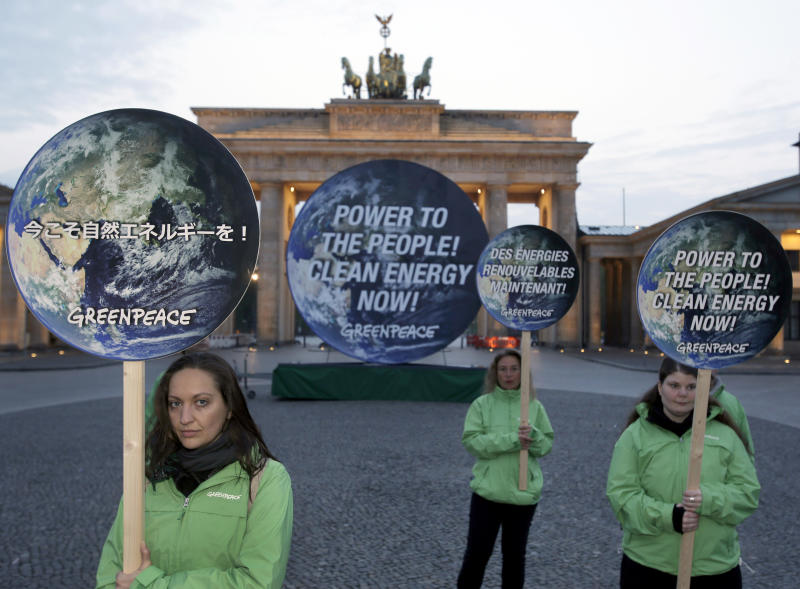 Activists of the international environmentalist organization Greenpeace pose with posters in front of the Brandenburg Gate in Berlin, Germany, Sunday, April 13, 2014, to support clean energy. After a one week meeting of the Intergovernmental Panel on Climate Change in Berlin the final document which is released on Sunday is expected to say that a global shift to renewable energy from fossil fuels like oil and coal are required to avoid potentially devastating sea level rise, flooding, droughts and other impacts of warming. (AP Photo/Michael Sohn)