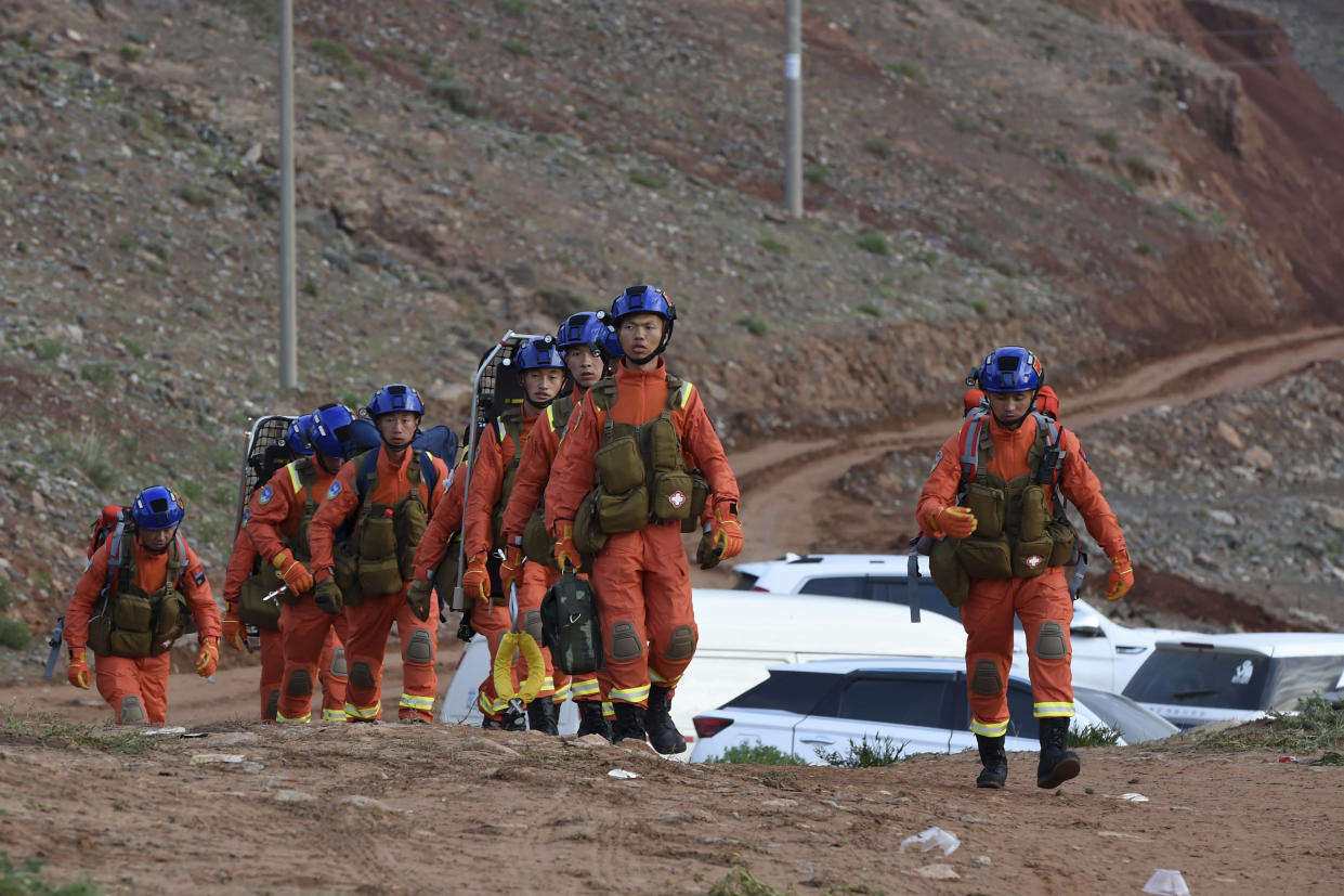 In this photo provided by China's Xinhua News Agency, rescuers walk into the accident site to search for survivors in Jingtai County of Baiyin City, northwest China's Gansu Province, Sunday, May 23, 2021. More than a dozen of people running a mountain marathon have died in northwestern China after hail, freezing rain and gale-force winds hit the high-altitude race, state media reported Sunday. (Fan Peishen/Xinhua via AP)