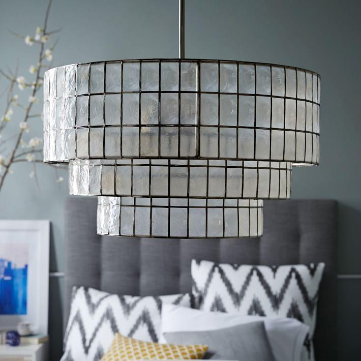 """<p>westelm.com</p><p><strong>$399.00</strong></p><p><a href=""""https://go.redirectingat.com?id=74968X1596630&url=https%3A%2F%2Fwww.westelm.com%2Fproducts%2Fcapiz-tiered-chandelier-w1144&sref=https%3A%2F%2Fwww.veranda.com%2Fhome-decorators%2Fadvice-from-designers%2Fg34482141%2Fboutique-hotel-style%2F"""" rel=""""nofollow noopener"""" target=""""_blank"""" data-ylk=""""slk:Get the Look"""" class=""""link rapid-noclick-resp"""">Get the Look</a></p><p>This stunning light fixture is made with hand-cut capiz shells by Filippino artisans and adds a touch of laid-black glamour to any room.</p>"""