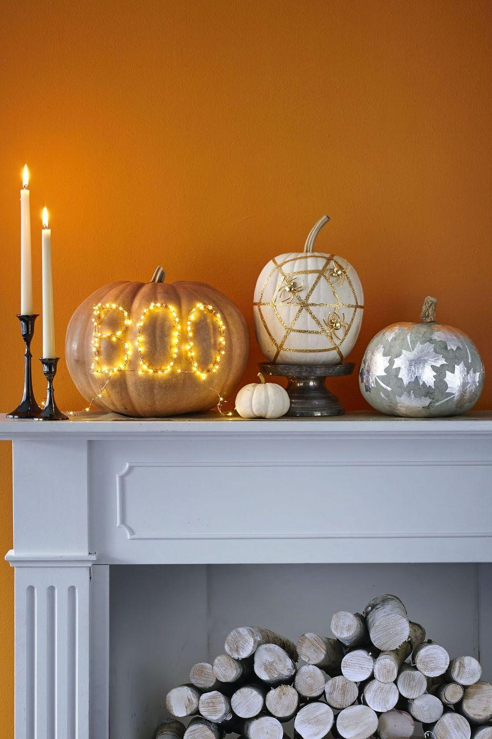 """<p>Use highlighter to spell out BOO on a pumpkin. Outline letters with straight pins, leaving about a ½-inch of pin sticking out. Wrap LED copper string lights around pins; repeat two to three times. Tuck battery pack behind the pumpkin. </p><p><a class=""""link rapid-noclick-resp"""" href=""""https://www.amazon.com/Ariceleo-Operated-Christmas-Centerpiece-Decoration/dp/B07S3R6MKJ?tag=syn-yahoo-20&ascsubtag=%5Bartid%7C10070.g.331%5Bsrc%7Cyahoo-us"""" rel=""""nofollow noopener"""" target=""""_blank"""" data-ylk=""""slk:SHOP STRING LIGHTS"""">SHOP STRING LIGHTS</a></p>"""