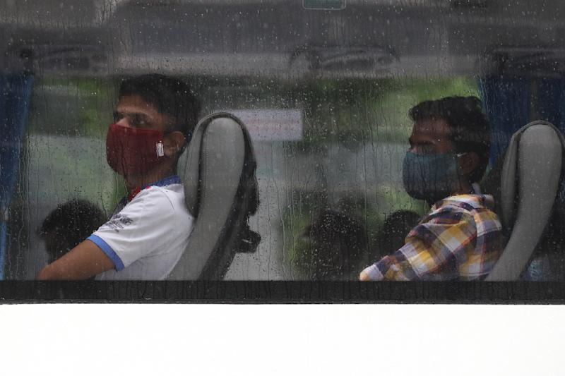 SINGAPORE - APRIL 27: Foreign workers wearing protective masks wait on a bus to be transferred from their dormitory on April 27, 2020 in Singapore. Singapore is now battling to control a huge outbreak in the coronavirus (COVID-19) local transmission cases among the migrant workers. (Photo by Suhaimi Abdullah/Getty Images)