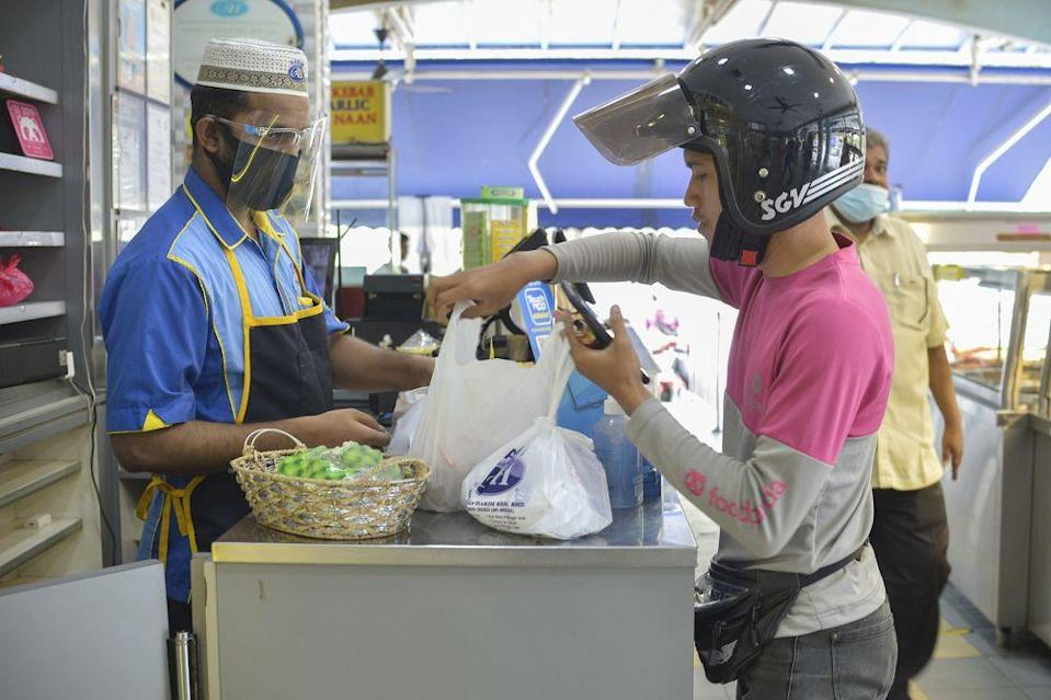 A food delivery rider picks up his order at Hakim Nasi Kandar, Shah Alam January 13, 2021. — Picture by Miera Zulyana