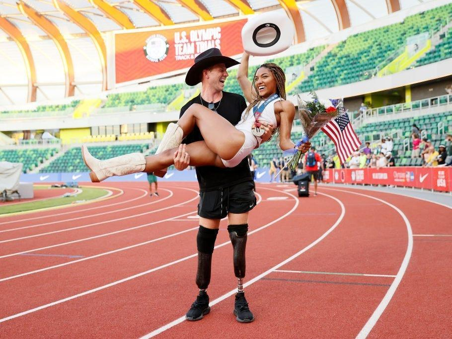 Hunter Woodhall holds girlfriend Tara Davis in his arms on a track field