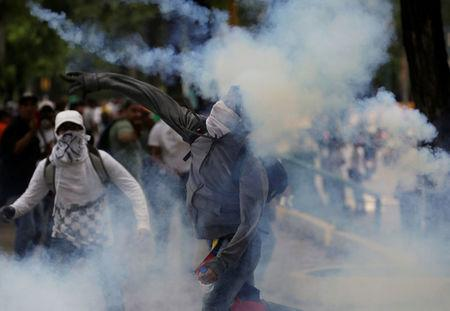 A demonstrator throws a tear gas canister back to police during clashes while rallying against Venezuela's President Nicolas Maduro in Caracas