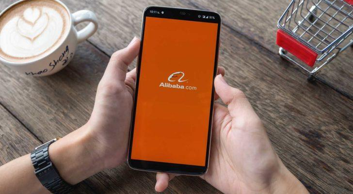 Alibaba (BABA) logo displayed on phone screen in person's hands