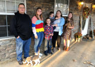 Keith Michael, left, poses with his children, from left, Jessica, Hunter, Houston, Sara and Holly, outside their home on Friday, Nov. 13, 2020, in Jonesboro, Ark. Among the victims of the coronavirus is Michael's wife, fourth-grade Arkansas teacher Susanne Michael, who died less than three months after celebrating the adoption of three of the children. (AP Photo/Adrian Sainz)