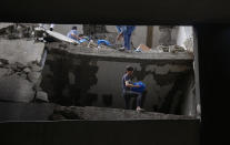 Palestinians inspect the destroyed building housing the offices of The Associated Press and other media after it was hit last week by an Israeli airstrike in Gaza City, Friday, May 21, 2021. A cease-fire took effect early Friday after 11 days of heavy fighting between Israel and Gaza's militant Hamas rulers that was ignited by protests and clashes in Jerusalem. (AP Photo/Hatem Moussa)