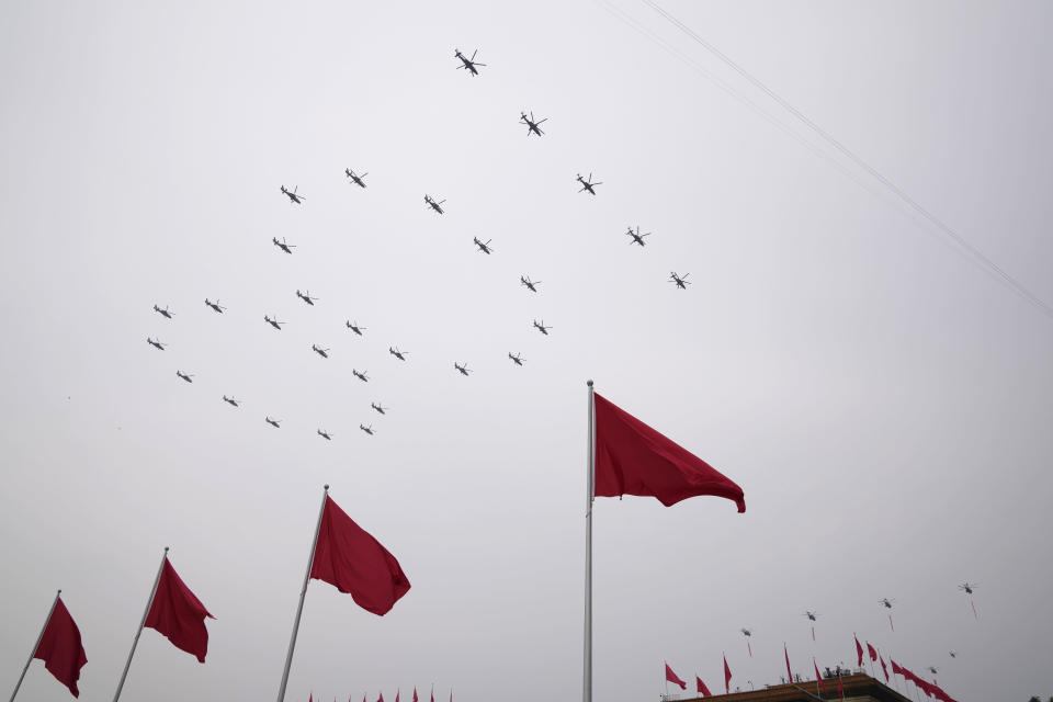 """Helicopters fly over Chinese flags at Tiananmen Square in the formation of """"100"""" during a ceremony to mark the 100th anniversary of the founding of the ruling Chinese Communist Party at Tiananmen Gate in Beijing Thursday, July 1, 2021. (AP Photo/Ng Han Guan)"""