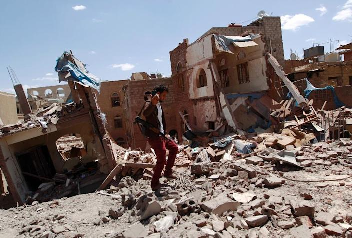 An armed Yemeni man walks atop the ruins of buildings destroyed in an air-strike by the Saudi-led coalition in Sanaa on September 10, 2015 (AFP Photo/Mohammed Huwais)