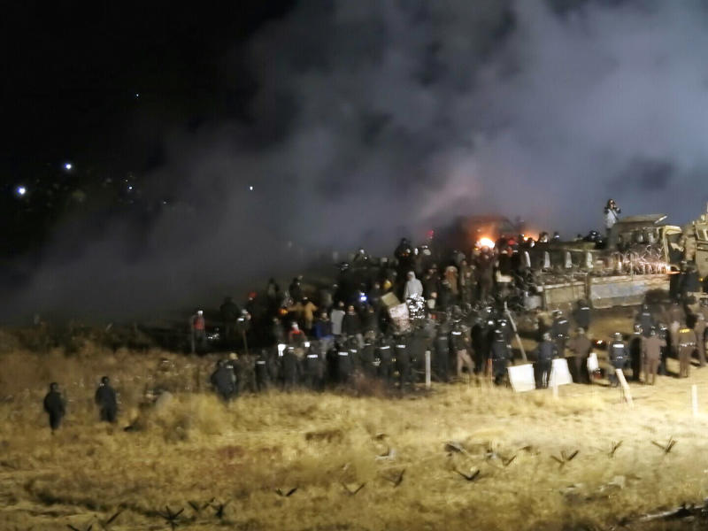 FILE - In this Nov. 20, 2016 file photo, provided by Morton County Sheriff's Department, law enforcement and protesters clash near the site of the Dakota Access pipeline in Cannon Ball, N.D. A western South Dakota sheriff is seeking to be dismissed from a lawsuit challenging new state laws that aim to prevent disruptive demonstrations against the Keystone XL oil pipeline similar to those a few years ago in North Dakota against the Dakota Access pipeline. Attorneys for Pennington County Sheriff Kevin Thom say he must enforce state laws but isn't responsible for defending them. They also argue the lawsuit is baseless. The American Civil Liberties Union and American Indian tribes maintain the legislation stifles free speech. (Morton County Sheriff's Department via AP, File)