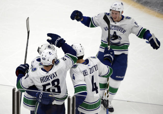 Vancouver Canucks defenseman Troy Stecher, top right, joins his teammates to celebrate a goal by center Bo Horvat (53) during the third period of an NHL hockey game against the Boston Bruins, Thursday, Nov. 8, 2018, in Boston. The Canucks won 8-5. (AP Photo/Elise Amendola)