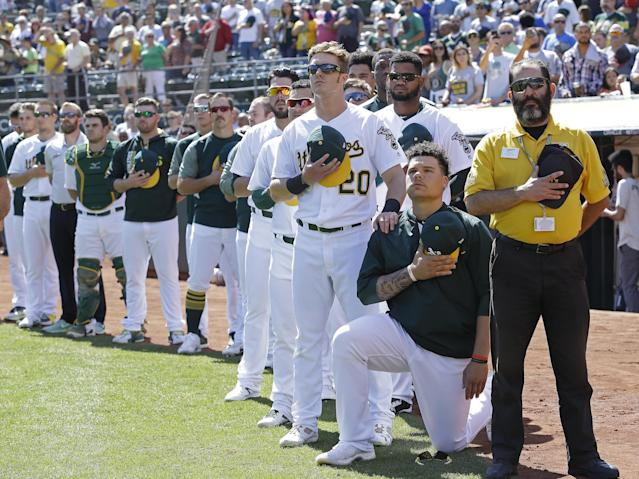 Oakland Athletics' Mark Canha (20) places his hand on the shoulder of Bruce Maxwell as Maxwell takes a knee during the national anthem prior to a baseball game against the Texas Rangers: AP